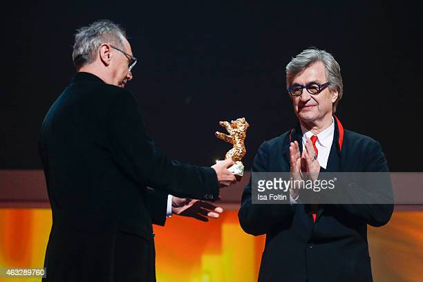 Wim Wenders recieves his Honorary Golden Bear from festival director Dieter Kosslick during the 65th Berlinale International Film Festival at...