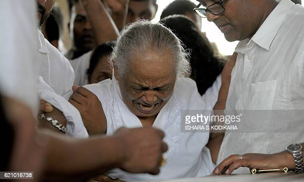 Wimala Amaradewa wife of legendary musician Amaradewa grieves during his funeral at Independence Square in Colombo on November 4 2016 Amaradeva has...