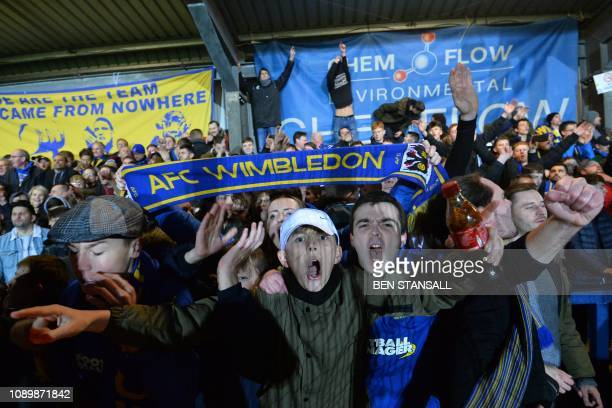 AFC Wimbledon fans celebrate their victory at the end of the English FA Cup fourth round football match between AFC Wimbledon and West Ham United at...