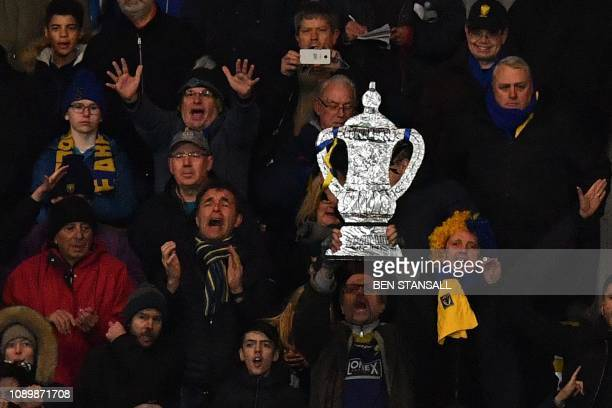 AFC Wimbledon fans cheer with one holding a homemade tinfoil FA Cup during the English FA Cup fourth round football match between AFC Wimbledon and...
