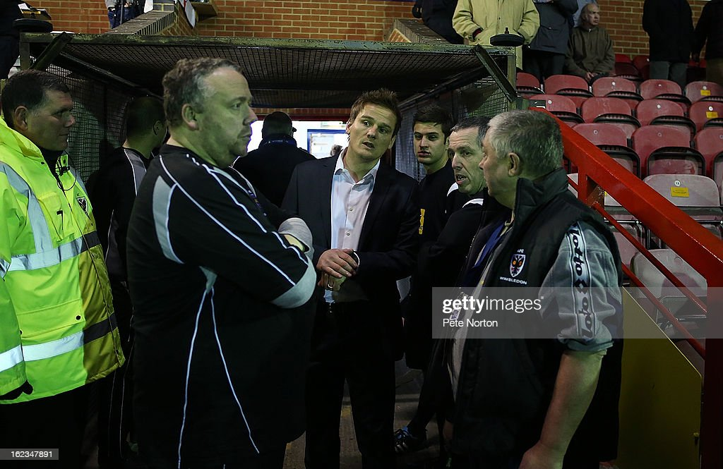 Wimbledon manager Neal Ardley (centre) looks on with referee Fred Graham (2nd right) after a floodlight faliure led to a 20 minute delay to the start of the game prior to the npower League Two match between AFC Wimbledon and Northampton Town at The Cherry Red Records Stadium on February 19, 2013 in Kingston upon Thames, England.
