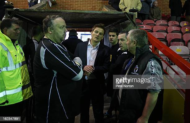 Wimbledon manager Neal Ardley looks on with referee Fred Graham after a floodlight faliure led to a 20 minute delay to the start of the game prior to...