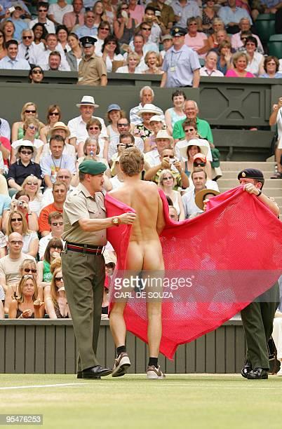 Wimbledon security men stop a streaker as Maria Sharapova of Russia plays against compatriot Elena Dementieva in the quarterfinals the Wimbledon...