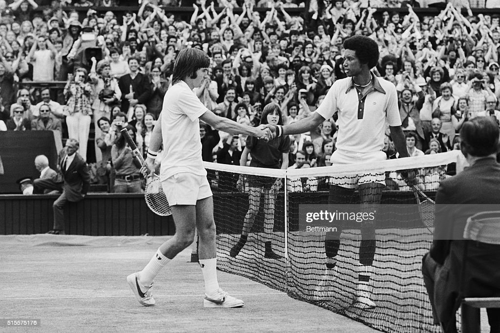 Artur Ashe, USA and Jimmy Connors, USA shake hands over the net here 7/5, after Ashe had won the men's singles title, with score 6-1,6-1,5-7,6-4. 7/5/1975