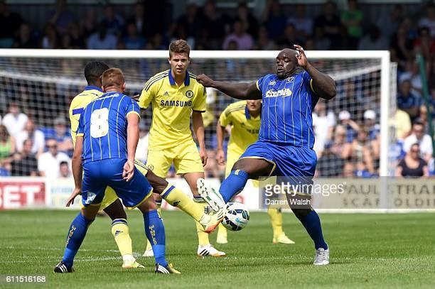 AFC Wimbledon's Adebayo Akinfenwa and Chelsea's Jeremie Boga battle for the ball