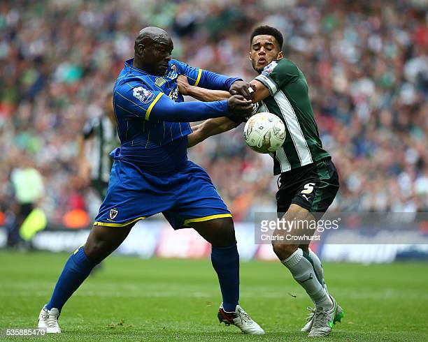 Wimbledon's Adebayo Akinfenwa battles for the ball with Plymouth's Curtis Nelson during the Sky Bet League 2 Play Off Final between Plymouth Argyle...