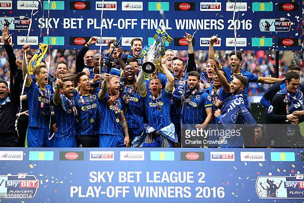 Wimbledon's Barry Fuller lifts the trophy high as he celebrates the team win and promotion with team mates during the Sky Bet League 2 Play Off Final...