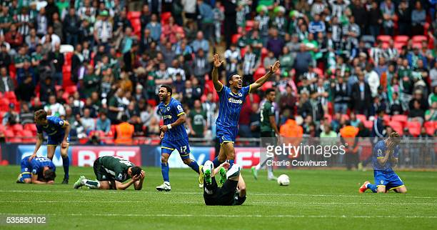 Wimbledon's Darius Charles celebrates the teams win at the final whistle as Plymouth players collapse to the floor dejected during the Sky Bet League...