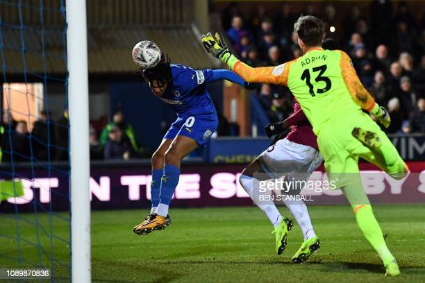 AFC Wimbledon's English defender Toby Sibbick heads the ball in to score their fourth goal during the English FA Cup fourth round football match...