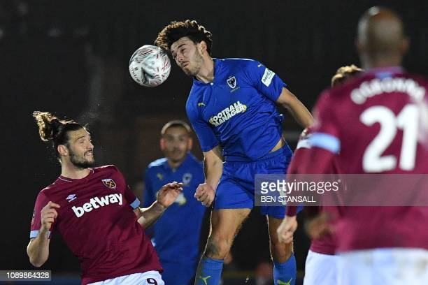 AFC Wimbledon's English defender Will Nightingale wins a header against West Ham United's English striker Andy Carroll during the English FA Cup...
