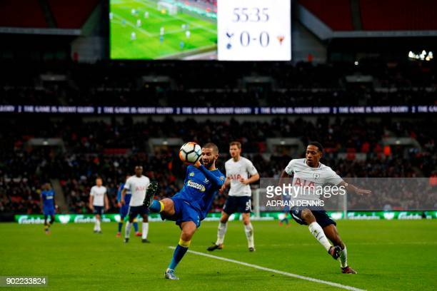 AFC Wimbledon's English midfielder George Francomb plays the ball under pressure from Tottenham Hotspur's English defender Kyle WalkerPeters during...