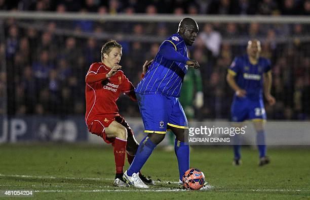 AFC Wimbledon's English striker Adebayo Akinfenwa vies with Liverpool's Brazilian midfielder Lucas Leiva during the English FA Cup third round...