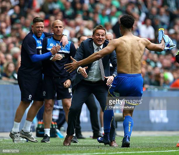 Wimbledon's Lyle Taylor celebrates scoring the first goal of the game with manager Neal Ardley during the Sky Bet League 2 Play Off Final between...
