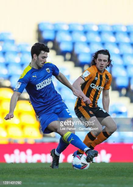 Wimbledon's Will Nightingale miss controls the ball under pressure from Hull City's George Honeyman during the Sky Bet League One match between AFC...