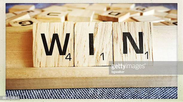 win spelled with scrabble tiles letters - game night stock photos and pictures