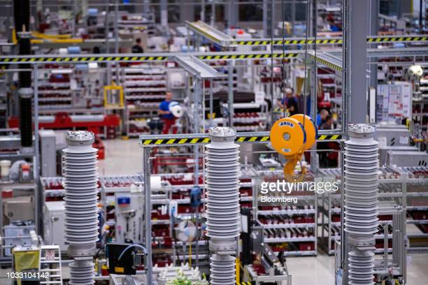 A winch hangs on the high voltage circuit breaker production line inside Siemens AG switchgear electronic power unit factory in Berlin Germany on...