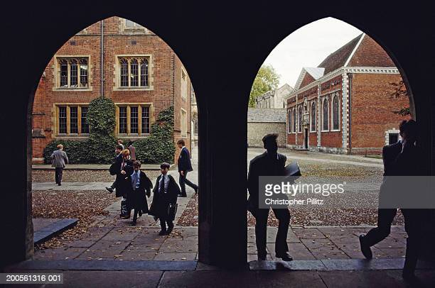 UK, Winchester College, Wiltshire, students and children walking in yard