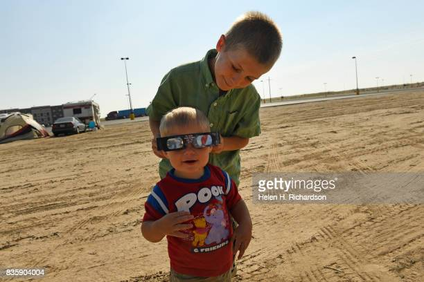Winchester Fenley tests out his solar eclipse glasses on his younger brother Wesley in preparation for tomorrow's solar eclipse at his family's camp...