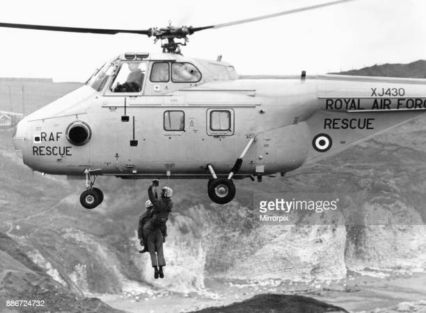 Winchman Norman Harris and Coastguard Bob Newsome being lifted into a RAF Westland Whirlwind HAR10 helicopter as it hovers over the cliffs at...
