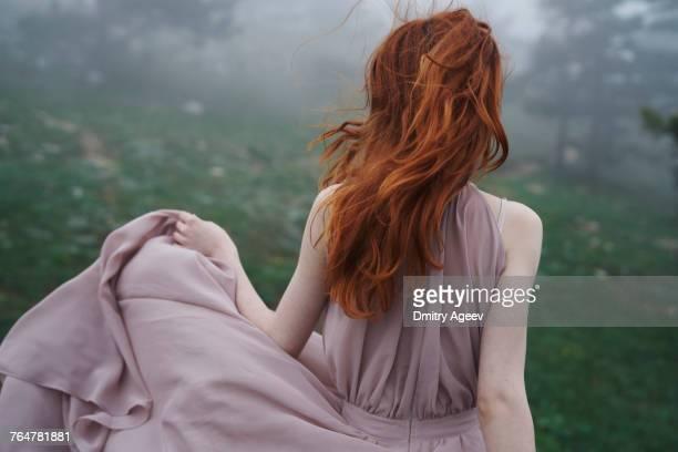 Wind blowing hair of Caucasian woman in field