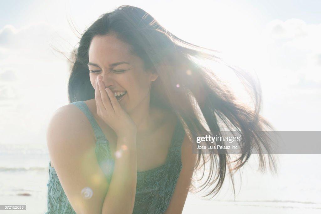 Wind blowing hair of laughing Hispanic woman : Stock-Foto