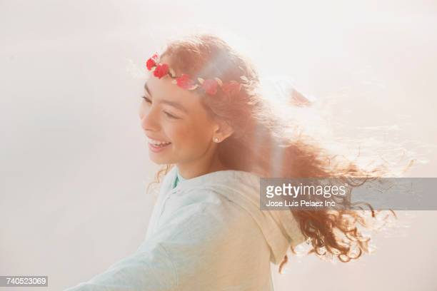 Wind blowing hair of smiling Mixed Race girl wearing flower headband