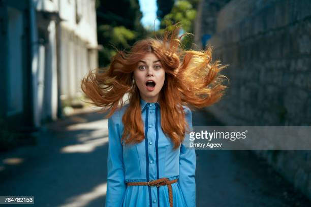 wind blowing hair of surprised caucasian woman - überraschung stock-fotos und bilder