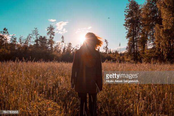 Wind blowing hair of woman standing in field