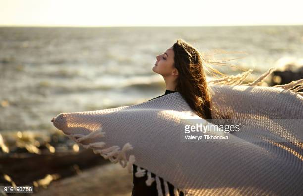wind blowing shawl of caucasian woman at beach - shawl stock pictures, royalty-free photos & images