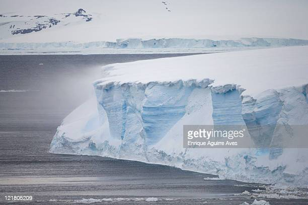 Wind blowing snow off icebergs in pack ice, Antarctic Sound, Antarctica