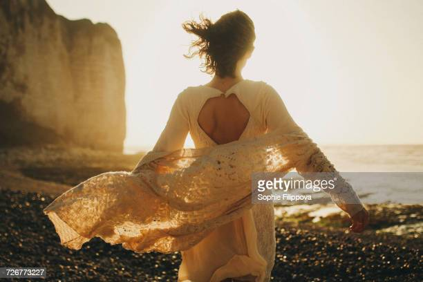 Wind blowing sweater of Caucasian woman at beach