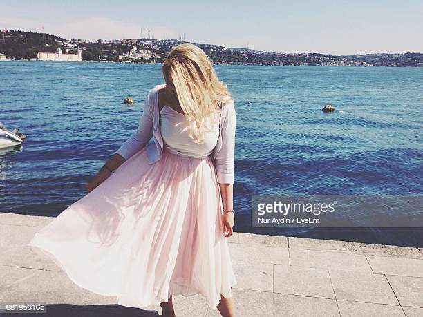 wind blowing womens skirt by the sea - windy skirt stock photos and pictures