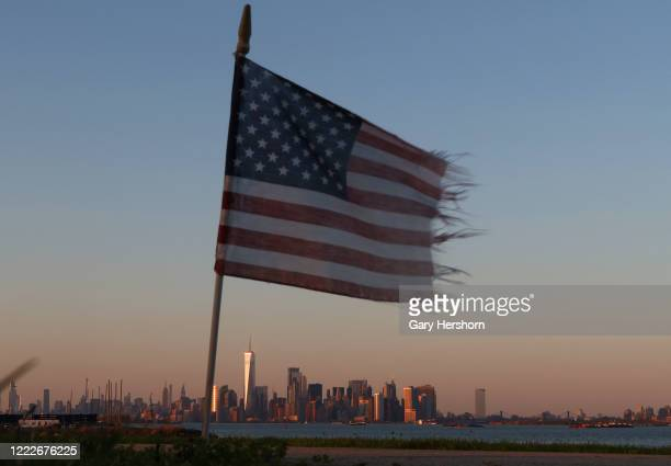 Wind blown American flag at the Tear Drop 9/11 Memorial flies over the skyline of New York City as the sun sets on May 3, 2020 in Bayonne, New Jersey.