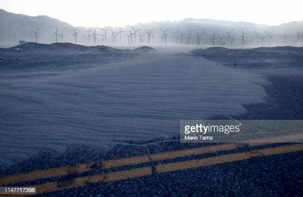 Wind blown sand partially covers a road near a wind farm in the Coachella Valley on May 7 2019 in Palm Springs California California's Fourth Climate...