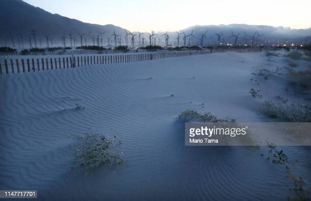 Wind blown sand partially covers plants near a wind farm in the Coachella Valley on May 7 2019 in Palm Springs California California's Fourth Climate...