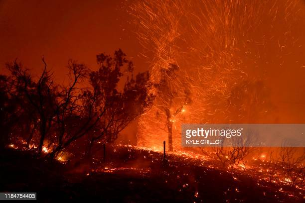 Wind blows embers as the Cave fire burns a hillside in Santa Barbara California on November 26 2019 The winddriven brush fire that started late on...