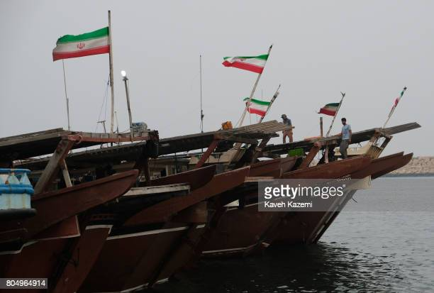 Wind blows into Iranian flags hanging on top of commercial lynch boats that are active in the Persian Gulf region on May 1 2017 in Qeshm Island Iran...