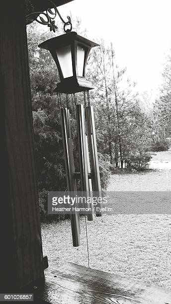 wind chime hanging against yard of house - heather harmon stock pictures, royalty-free photos & images