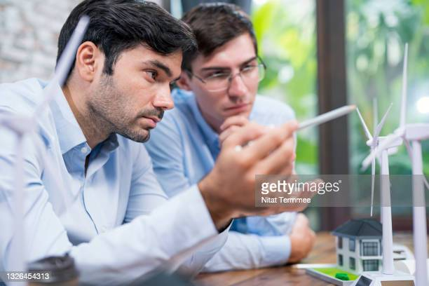 wind energy engineers having a discussion and exchange ideas of designs wind farms or their components on the wind turbine model before starting the production processes.  renewable sources of wind energy solutions concepts. - responsibility stock pictures, royalty-free photos & images