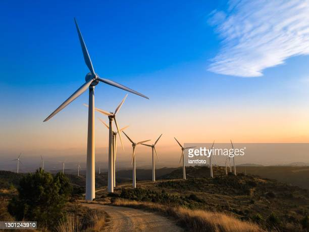 wind farm at sunset. - renewable energy stock pictures, royalty-free photos & images