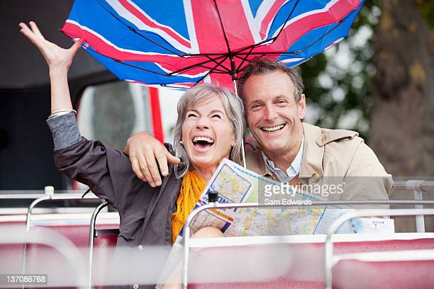Wind flipping British flag umbrella over happy couple with map on double decker bus