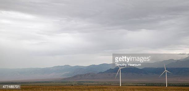 wind generators with mountains and stormy sky - timothy hearsum stock photos and pictures