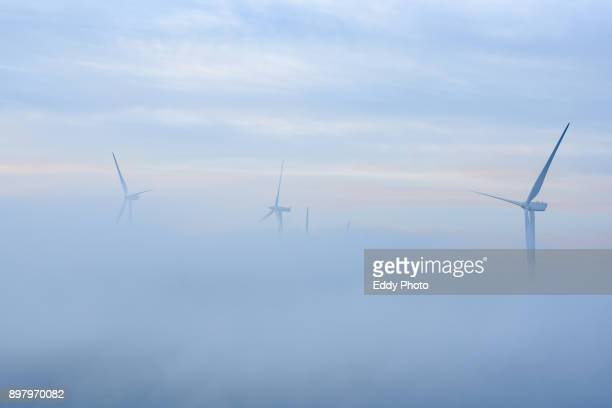 wind power generators in a foggy morning - alternative energy stock photos and pictures