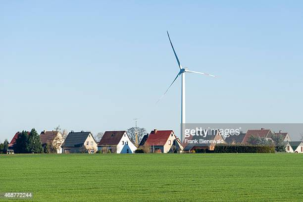 RAECKELWITZ SAXONY GERMANY A wind powerplant behind village houses in agricultural landscape