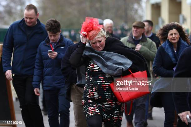 A wind swept lady holds onto her hat as crowds arrive on Ladies Day of the Cheltenham Festival at Cheltenham Racecourse on March 13 2019 in...