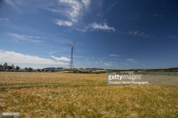 wind turbine against blue sky with clouds in field - christina luft stock-fotos und bilder