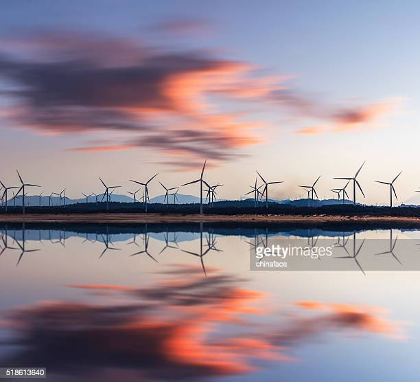 wind turbine and electrical towers on sunset - windmills stock photos and pictures