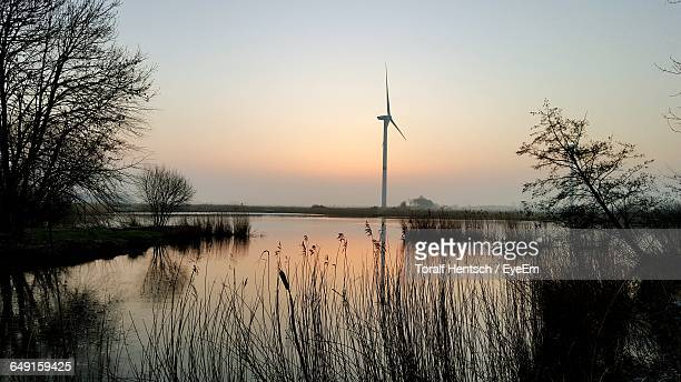 wind turbine by lake against sky during sunset - husum stock-fotos und bilder