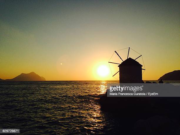 wind turbine by sea against sky during sunset - francesca mills stock pictures, royalty-free photos & images