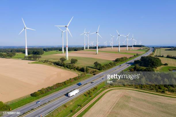 wind turbine farm near the highway - environment stock pictures, royalty-free photos & images